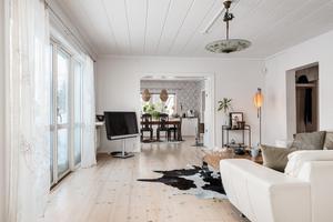 Matrummet och vardagsrummet i fil, med trägolv och ljusinredning. Rummen har stora fönsterpartier och utgång till altanen från båda rummen.