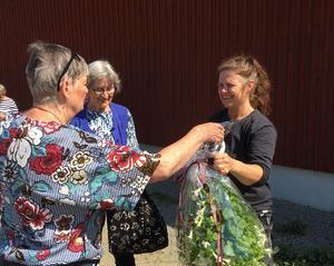 Ordförande Maud Kvarnäng tackar Kristina Mickelsson från Vallens Gård med en blomma efter den guidade visningen.