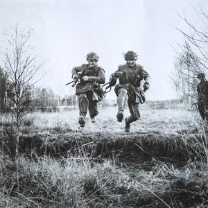 Tore Södersten till vänster och Thure Klintman till höger hoppar över ett dike på Myran i Falun under en militärövning år 1957. I handen har de varsin k-pist. Foto: Leif Forslund
