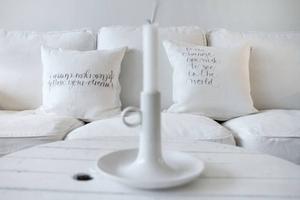 FINA BUDSKAP. Kuddarna har formgivaren Ylva Skarp gjort och liksom resten av Lise-Lotts vita hem finns det en vacker text till och med på kuddarna.