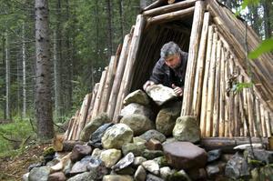 Håller värmen. Torbjörn Persson bygger på kolarkojans eldstad. Långt efter att brasan har slocknat ska stenarna ge ifrån sig värme till de övernattande turisterna.