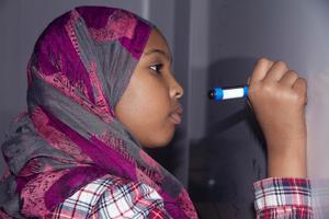 Maryan Abdirahman, 12, försöker lösa matematiska ekvationer framme vid whiteboardtavlan. Varje vecka får hon hjälp med sina läxor på Knytpunkten på Råby.