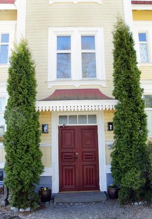 Ytterdörren pryds av ett näpet baldakintak med en kant som påminner om tårtpapper.