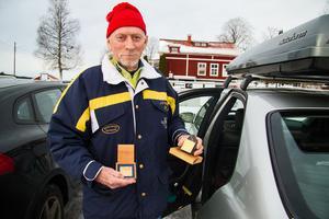Per Nilsson visar upp sina två plaketter. Den vänstra fick han när han hade åkt 20 lopp, den högra när han åkte sitt 30:e Engelbrektslopp.