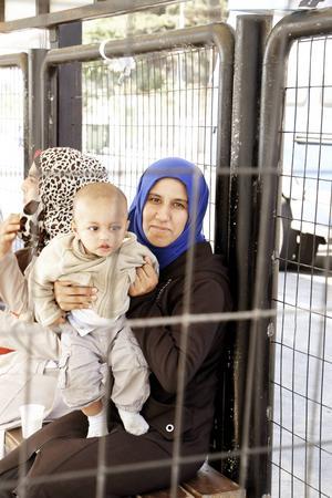 Haifa med sin bebis Walid sitter i väntkuren nere vid hamnen.