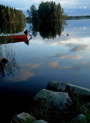 Stannade upp och tog en bild över den blanka vattenytan och där en röd båt lyser upp i allt blå.