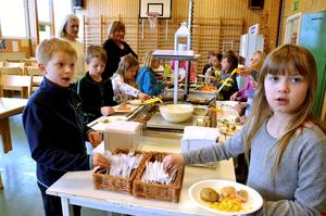Tillfälllig matsal. Kokt lax och potatis serverades under onsdagen i Tulpanens gymnastikhall.Joel Gunnarsson och Amanda Andersson får äta på engångstallrikar.