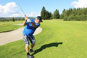 John Carlsson svingar golfklubban vid andra hålet.