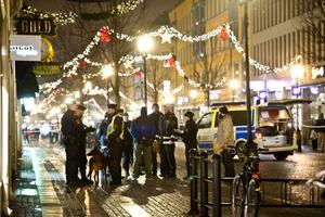 Poliser utanför butiken på Drottninggatan där den skjutne föll ihop efter skjutningen mitt i julhandeln under lördagen.
