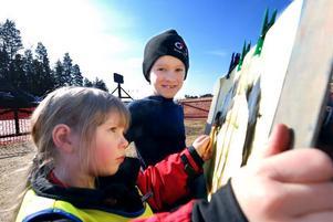 Barnpassning. Lina och David Tegmark målar med vattenfärg på dukar som står uppställda i solen. De har också hunnit med att fika och spela fotboll.