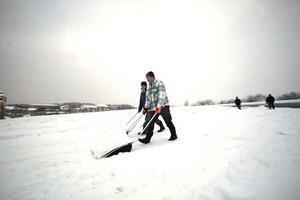 Anders Johansson och Stefan Strandqvist gör sitt bästa för att få bort snön på Åhlénstaket. På vissa ställen är snölagret omkring 70 centimeter djupt.