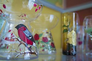 Det är Helena Egnell Larsson som målar på glas. Det är bara ett av alla hantverk hon gillar att hålla på med under pyssleträffarna.