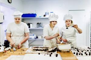 Josefin Erlandsdotter, Elin Hansson och Maja Olsson doppar praliner i choklad.