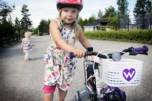 Juni Sahlberg visar stolt upp sin nya cykel. Lillasyster Ester håller sig i bakgrunden.