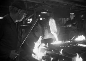 Det var sotigt, hett och rökigt på Skoglund & Olsons gjuteri i Gävle. Massan som hälls ner i gjutformen på den här bilden från 1967 har en temperatur på närmare 1 500 grader. Mannen närmast kameran är förmannen Harry Eriksson.Foto: Arbetarbladet/Stefan Tkatjenko