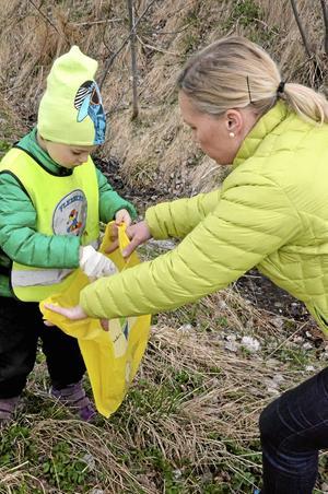 Cecilia Karlsson hjälper Einar Björkdahl att hålla upp påsen så att han får ner allt skräp han hittat.