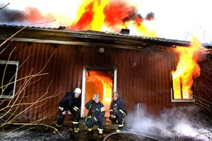 NOVEMBER.  somras brann det i det gamla huset som varit både skogvaktarboställe och klubblokal för Skidkamraterna. Skadorna var för stora för att huset skulle kunna räddas. Lösningen blev att försäkringsbolaget, Länsförsäkringar, överlät huset till räddningsstjänstens  för övning. Den 20 november var det dags. Ledaren Hasse Johansson gick in med bensindunken för att tända på. Det gick inte så bra. Tändaren fungerade inte.  Att sätta eld på hus är ju inte vårt jobb, sa brandmännen, och gick ut till åskådarna för att hitta en fungerande tändare.I vanliga fall har brandmännen inte tid att posera framför ett brinnande hus, men Andreas Jorstedt, Ola Johansson(länsförsäkringar) och Johan Kallin hade läget under kontroll.FOTO: Britt Mattsson