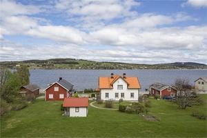 Den vita villan ligger fint med egen sjötomt, brygga, båthus och två gårdshus.
