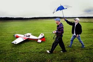 SKYDD FÖR REGNET. Stugfogde Alvar Björk håller upp ett paraply för Fredrik och sändaren. Snart är det dags för start på gräsmattan.
