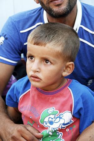 Mahir, 3, sitter med sin pappa i hamnen.