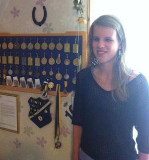 Viktoria Karlsson bredvid sin imponerande prissamling.
