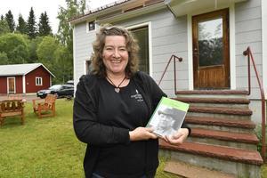 Marit Norin på Porfyrmuseet med boken om och av  Frost Anders. Anteckningar sopm återfans i den röda vedboden i bakgrunden. Anteckningsboken finns nu på Porfyrmuseet.