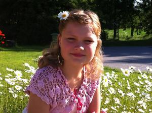 Vår sommarflicka Lillith! Påväg till skolavslutningen i Irstaskolan. Poserar mitt i prästkragshavet på vår framsida, fin klänning och blomma i håret en härlig känsla av sommar och sol! Ledigt! Härligt! Lite pirr av förväntan och man gör sig extra fin! (på bilden Lillith Kiiveri Eriksson, 11 år)