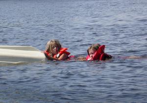 Ida och Maria tycker att bada. Lilla båten har de vänd upp och ner.