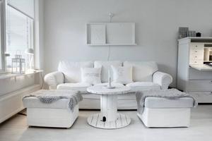 AVSLAPPNANDE. Vardagsrummet är öppet och går helt i vitt, förutom de två grå fårskinnsfällarna.