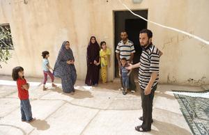 Utanför huset har Mahmoud satt upp ett tak till skydd från solen. Det blir som ett uterum där familjen ofta vistas på dagarna. Från vänster: Abir 6 år, Hasnaa 8 år, Oum Muhammed, fru Menal, Bayan 12 år, Faysal 3 år, pappa Mahmoud och kusin Kamel.