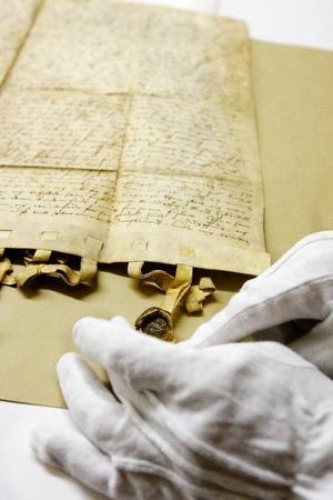 Protokollen från landstingets möten har förändrats en hel del från 1500-talets slut. Här visar Georg Hansson ett beslut från ett ting vid Kungsgården på Frösön anno 1599. Alla närvarande har bekräftat beslutet med personliga sigill i vax.