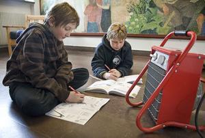 En värmefläkt kan vara bra att ha mot stela fingrar när man ska göra läxor, tycker Edvin Segerkvist och Mattias Öberg, två av eleverna i Segersta skola.