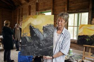 Eva Sollander visar en bild som Herman Englund har målat.
