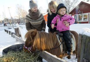 Maja Jonsdotter-Norberg sitter fint på hästen Rödluvan. Mamma Anna Norberg assisterar och hästskötare är Malin Ordeus.