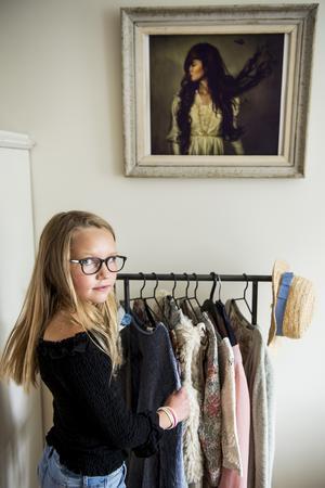 Elsi har samlat sina favoritkläder på en hängare. På väggen sitter ett print från Lisa Love inramat i ett loppisfynd.