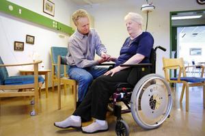Sjukgymnast Göte Hellzén hjälper Ella Svelander, som vårdas på sjukhemmet efter en stroke, med hennes arm och hand. Behandlingen är inte allt för angenäm, men nödvändig.