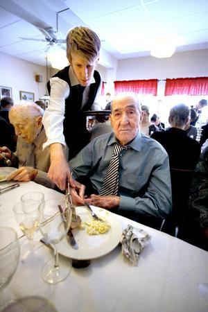 Finklädd. Ernst Öberg, som fyllt 100 år, mår gott på festen när han serveras av Daniel Bergman.