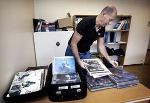 Polisinspektör Lars Karlsson bläddrar i den stora högen med vinylskivor, som nu finns beslagtaget hos polisen i Ludvika.