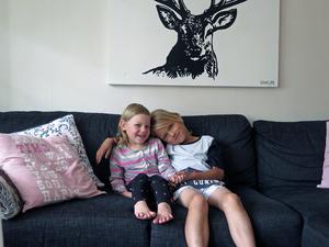 Minea och  Julian i soffan hemma i vardagsrummet.
