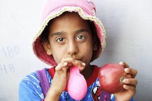 Rezan, 8, och hennes syskon har fått ballonger av några privatpersoner som delar ut mat och annat i hamnen.