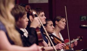 Violinisterna Elina Vaarama, Evelina Ekström och läraren Karin Nilsson (längst till höger) tittar på sina uppträdande kollegor.