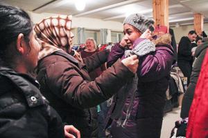 Fatima Ahmadi och Omndlbanin Najasi hjälper Jalda Ahmadi att prova ut en ny mössa.