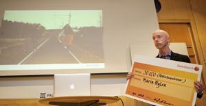 Jonny Gahnshag med prischecken framför den alternativa bilden av Dalarna där två unga kullor olagligt beträder Trafikverkets spår