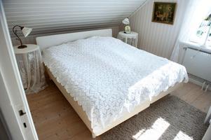 Sängöverkastet har Lars-Olovs mormor virkat och som sängbord har Monica två gamla pelarbord som hon hängt skira gardiner över.