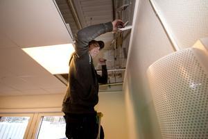 Thomas Norström på Vatten och värme i Norberg monterar nya värmerör i kaféet.