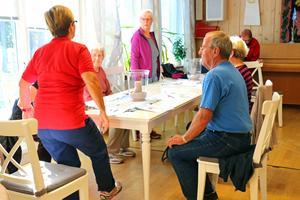 Fysioterapeuten Gunilla Häll visar en balansövning där en ska sitta ner och ställa sig upp från stolen.