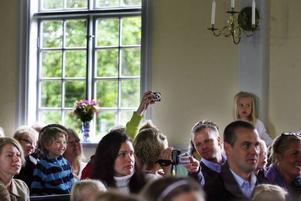Oslättfors kyrka är fullsatt av föräldrar, syskon och andra som vill vara med på skolavslutningen. Som sig bör är det många som dokumenterar barnens framträdanden.