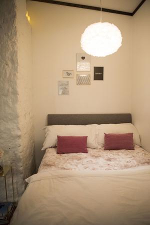Tavlorna sitter i grupp ovanför sängen. Towa gillar bilder med text.
