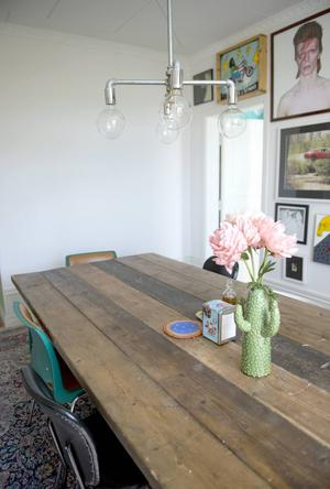 Ett vitt ellipsformat matbord har bytts ut mot ett stort rustikt bord som en snickare har byggt med gamla plankor från byggställningar.