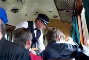 Många resande. Martin Pålsson är en av konduktörerna på museibanan i Roslagen. Här har han fullt upp med att klippa biljetter i en av de välbesatta vagnarna. Foto:Gunne Ramberg